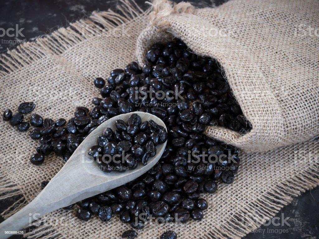 Tasche mit Kaffeebohnen aus der Tasche auf den steinernen Tisch und Holzlöffel - Lizenzfrei Alt Stock-Foto