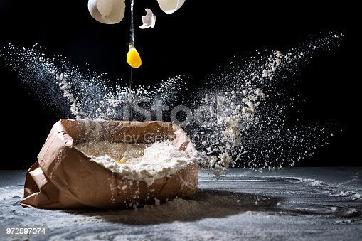 istock Bag with flour and egg flying in flour on black background. Flour splash. Cooking, baking 972597074
