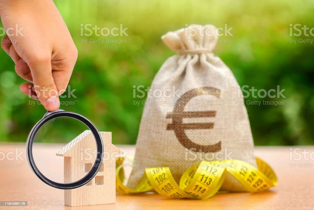Bag with money and tape measure with a wooden house. Market crisis....