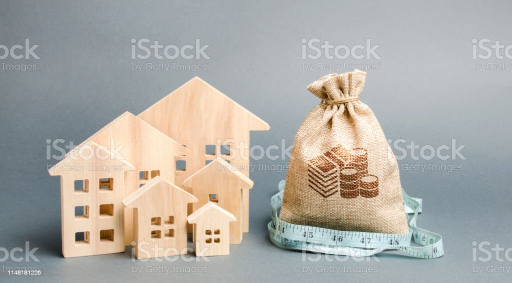 Bag with money and tape measure with a wooden houses. The concept of...