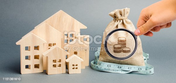 istock Bag with money and tape measure with a wooden houses. The concept of a limited real estate budget. Low subsidies. Lack of investment in construction. Market crisis. Bankruptcy 1151361610