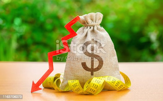 istock Bag with money and tape measure with arrow to down. Falling wages and welfare. Low profits and liquidity of investments. The concept of bankruptcy. Bad business payback. Capital outflow. Dollars 1163706073