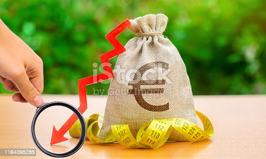 istock Bag with money and tape measure with arrow to down. Falling wages and welfare. Low profits and liquidity of investments. The concept of bankruptcy. Bad business payback. Capital outflow. Euro 1164095285