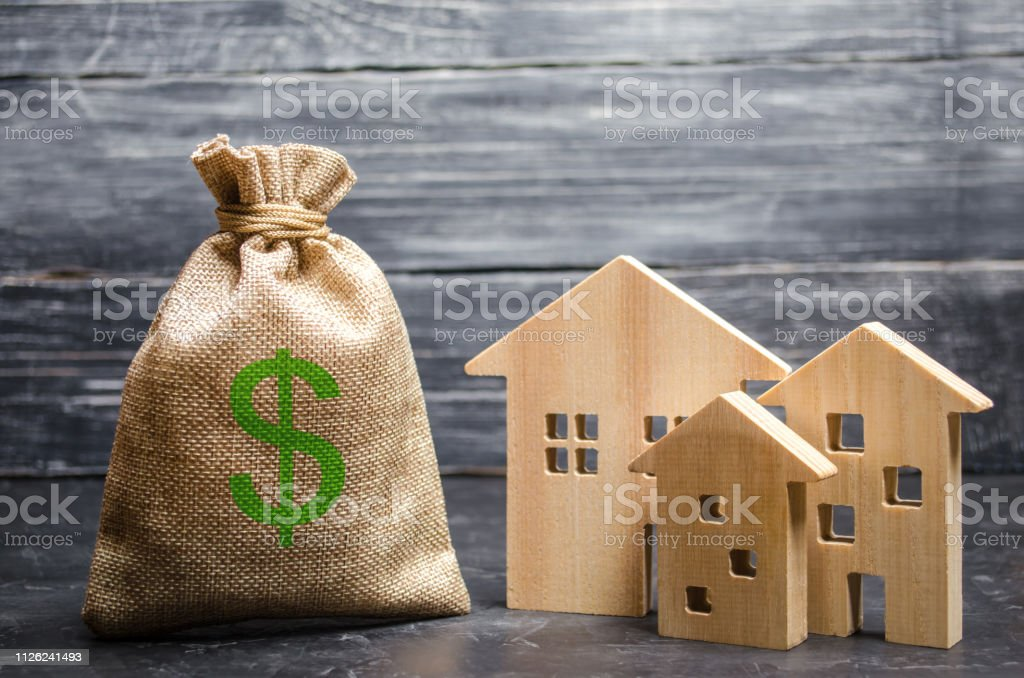A bag with money and three houses. Concept of real estate acquisition and investment. Affordable cheap loan, mortgage. Taxes, rental income. Building houses. Municipal budget of the community. stock photo