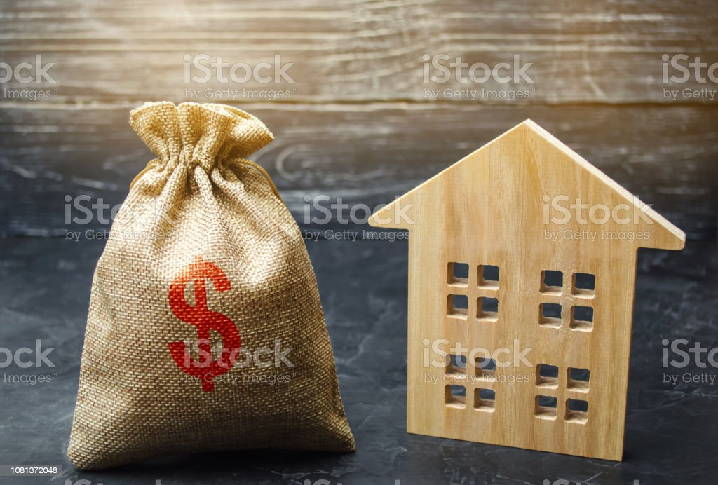 A bag with money and wooden house. Selling a house. Apartment purchase. Real estate market. Rental housing for rent. Home prices. Mortgage interest. Purchase demand. Property valuation. Insurance stock photo