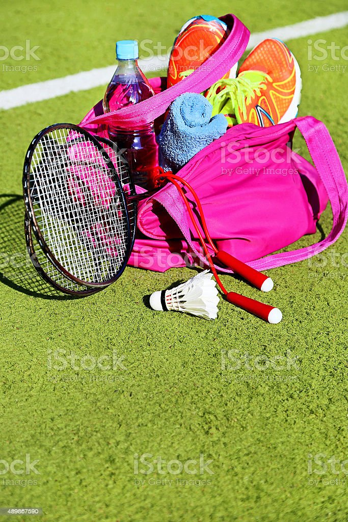 Bag with sports equipment on the sports courts background. Badminton...