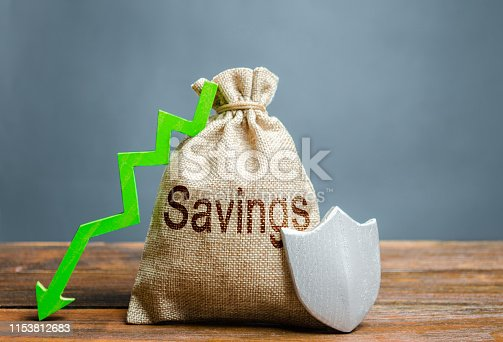 1145921132istockphoto Bag with the inscription savings, shield and green down arrow. Guaranteed protection of personal savings, investments. Protection of business and capital, respect for private property. Reduced risk 1153812683