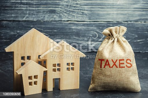 istock Bag with the money and the word Taxes and wooden houses. Taxes on real estate, payment. Penalty, arrears. Register of taxpayers for property. Law-abiding, evasion of payment. Court law. Luxury tax. 1083390656