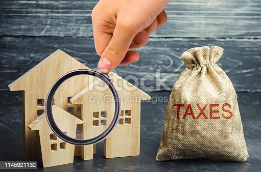 istock Bag with the money and the word Taxes and wooden houses. Taxes on real estate, payment. Penalty, arrears. Register of taxpayers for property. Law-abiding, evasion of payment. Court law. Luxury tax. 1145921132