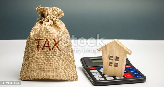 istock A bag with the word Tax and calculator with a house. Taxes on real estate, payment. Penalty, arrears. Register of taxpayers for property. Law-abiding, evasion of payment. Court law. Luxury tax 1124709326