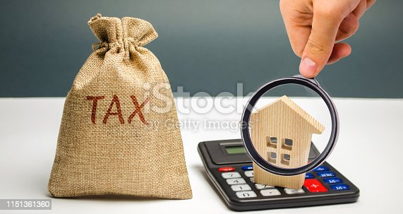istock A bag with the word Tax and calculator with a house. Taxes on real estate, payment. Penalty, arrears. Register of taxpayers for property. Law-abiding, evasion of payment. Court law. Luxury tax 1151361360