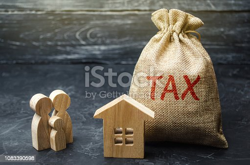 istock A bag with the word Tax and family stand near the house. Taxes on real estate, payment. Penalty, arrears. Register of taxpayers for property. Law-abiding, evasion of payment. Court law. Luxury tax. 1083390598