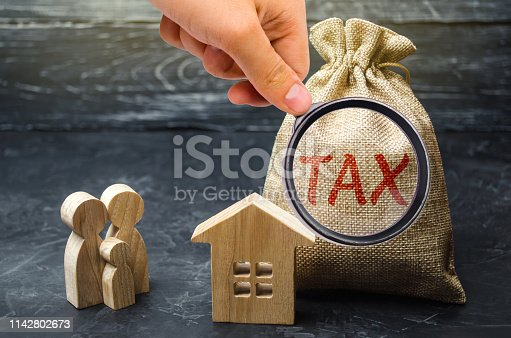 istock A bag with the word Tax and family stand near the house. Taxes on real estate, payment. Penalty, arrears. Register of taxpayers for property. Law-abiding, evasion of payment. Court law. Luxury tax. 1142802673