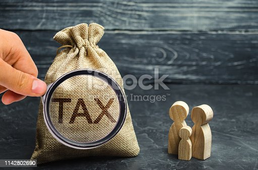 istock A bag with the word Tax and family. Taxes on real estate, payment. Penalty, arrears. Register of taxpayers for property. Law-abiding, evasion of payment. Court law. Luxury tax. 1142802690