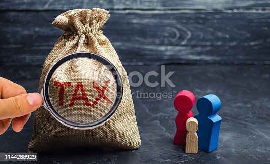 istock A bag with the word Tax and family. Taxes on real estate, payment. Penalty, arrears. Register of taxpayers for property. Law-abiding, evasion of payment. Court law. Luxury tax. 1144288929