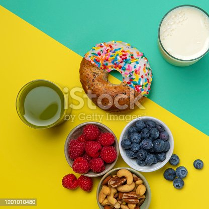 This is an overhead colorful photo of a split diagonal image showing half of a donut and half of a bagel seamlessly joined together. One half of the side is showing healthy food and the other half of the side is showing junk food