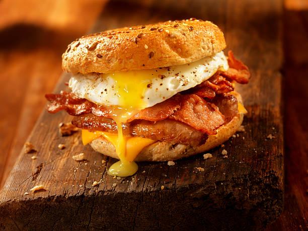 bagel, tocino, salchichas y sándwich de huevo - desayuno fotografías e imágenes de stock
