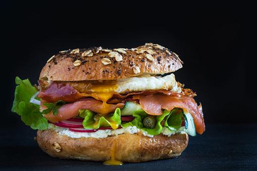 Bagel burger on black background.