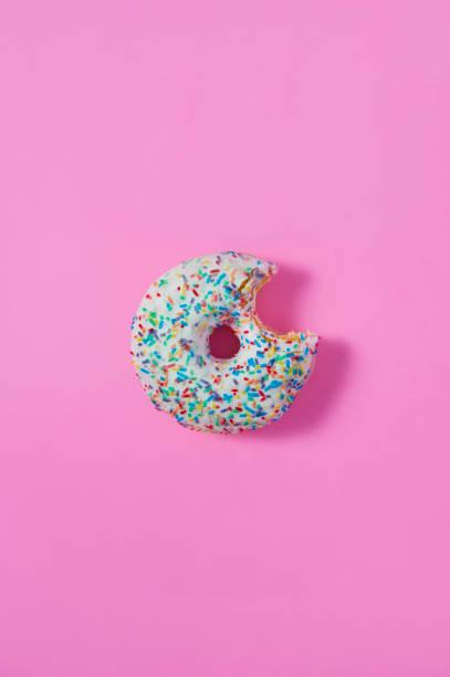 ein bagel mit einem biss auf rosa hintergrund isoliert. - löcherkuchen stock-fotos und bilder
