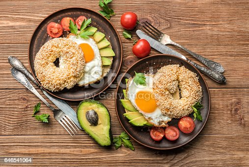 istock Bagel with avocado and egg on the wooden background. 646541064