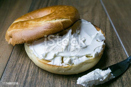 Front view, close up of bagel with cream cheese and spreading knife