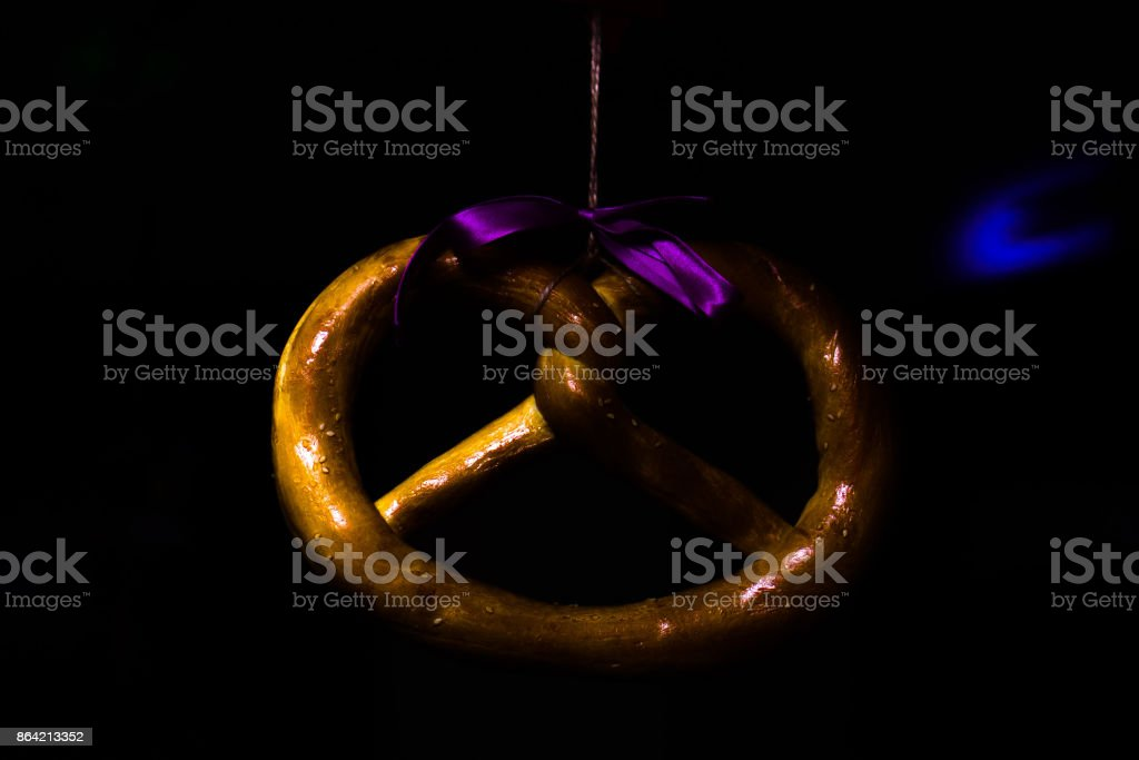 bagel with sesame whist on a rope with a bow in a low key royalty-free stock photo