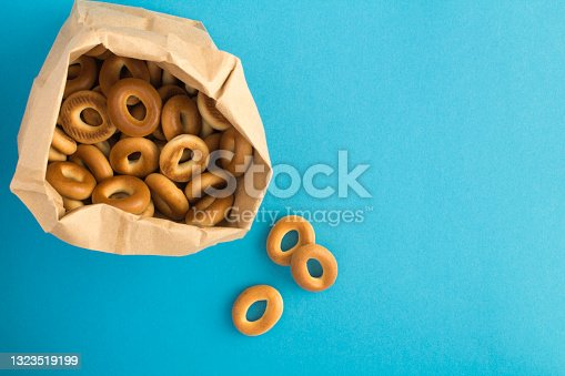 istock Bagels  in the paper package  on the blue background. Top view. 1323519199