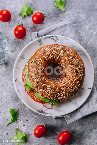 istock Bagels with avocado, tomatos, radish and green leaves on marble plate on concrete table background. Healthy lunch. Delicious balanced food concept. Top view 1133334819