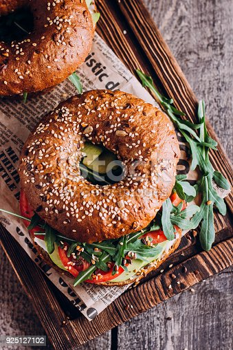 istock Bagels with cream, avocado, tomatos and arugula on wooden board and table background. Healthy breakfast food. Top view and Copy space 925127102