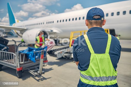 Back view of an airport male worker controlling the luggage uploading onto the conveyor belt