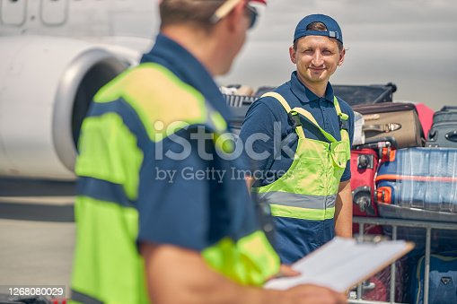 Smiling male worker in uniform looking at his colleague with a clipboard in his hand