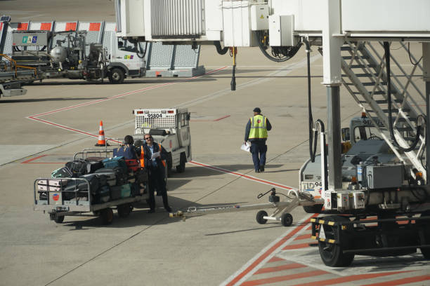 Baggage handling at the Paris Charles de Gaulle Airport, also known as Roissy Airport, with workers on the runway. stock photo
