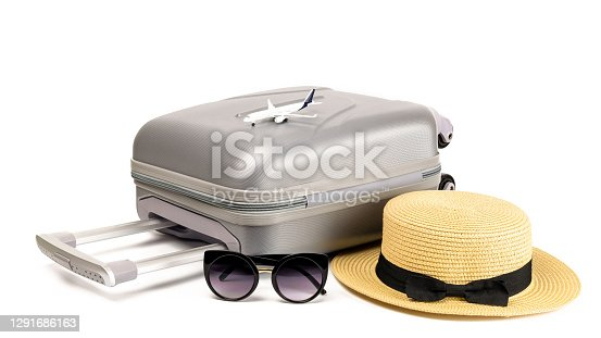 Baggage isolated. Travel accessories with suitcase, straw hat, toy airplane in minimal trip vacation concept isolated on white background. Summer vacation and product advertisement concept