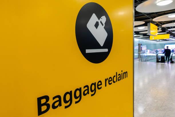 REGISTRO DE RECLAMO DE BAGGAGE, AEROPUERTO DE HEATHROW, 21 DE FEBRERO DE 2019, Señal de recogida de equipaje y pasajero con maleta rodante en la Terminal 5 del Aeropuerto de Heathrow, Londres, Inglaterra, Gran Bretaña, Europa - foto de stock