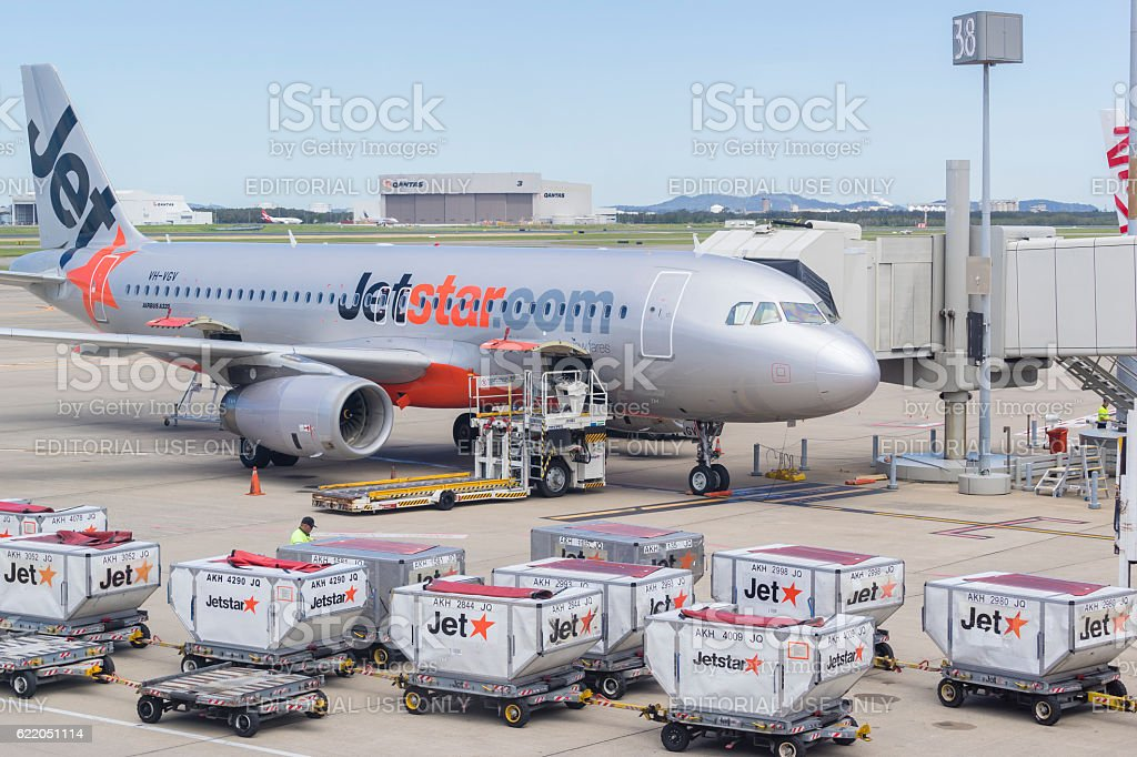 Baggage trucks and Jetstar aircraft at Brisbane Airport stock photo