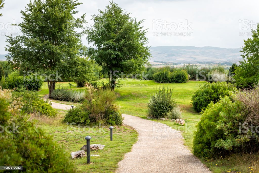 Bagno Vignoni Italy Medieval town by San Quirico d'Orcia, Val d'Orcia, Tuscany with green summer park and trail path landscaped garden stock photo