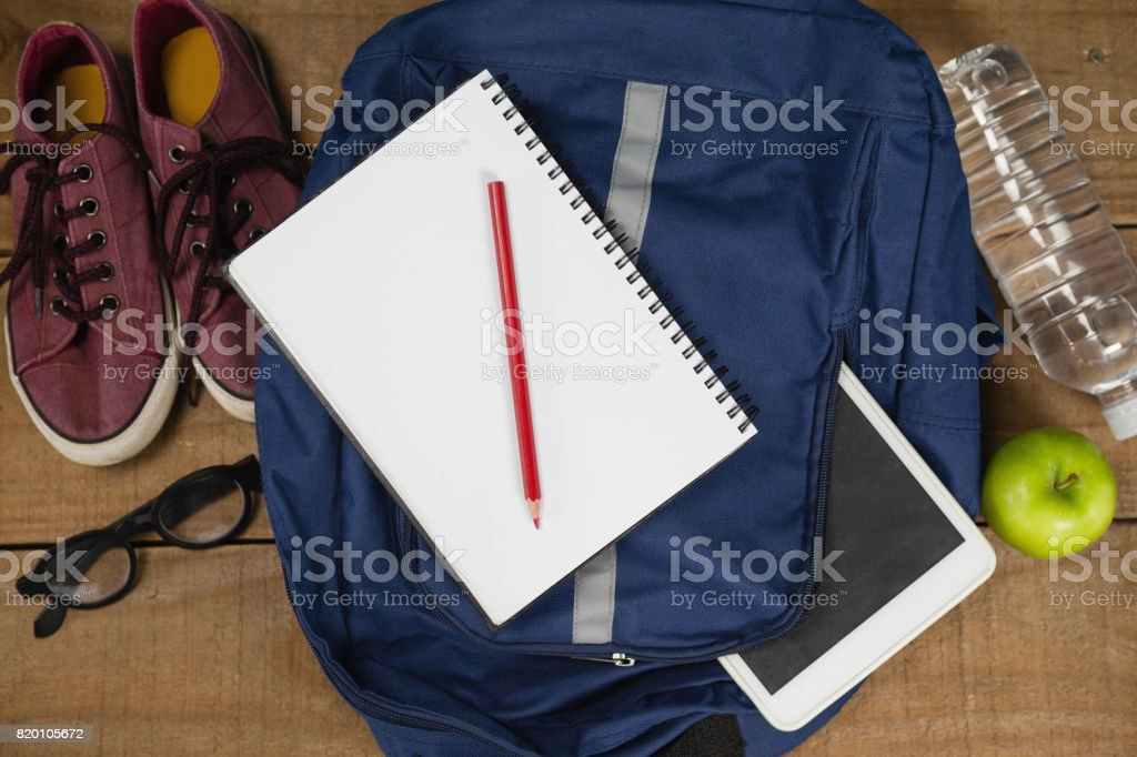 Bagpack, Diary, shoes, spectacles, digital tablet, apple and water bottle stock photo