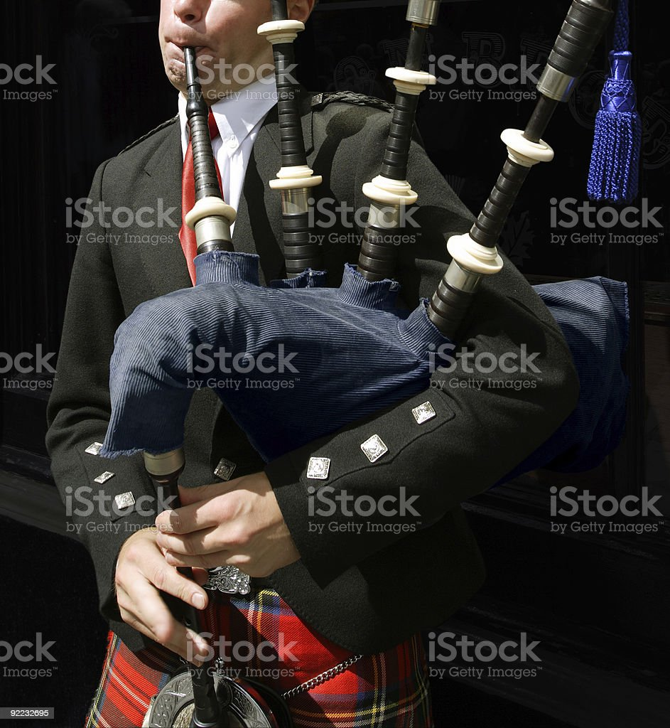 Bagpiper blowing his pipes stock photo