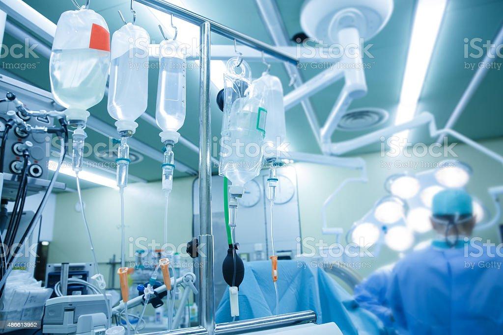 IV bolsas y frascos de montaje sobre polos durante la cirugía real - foto de stock