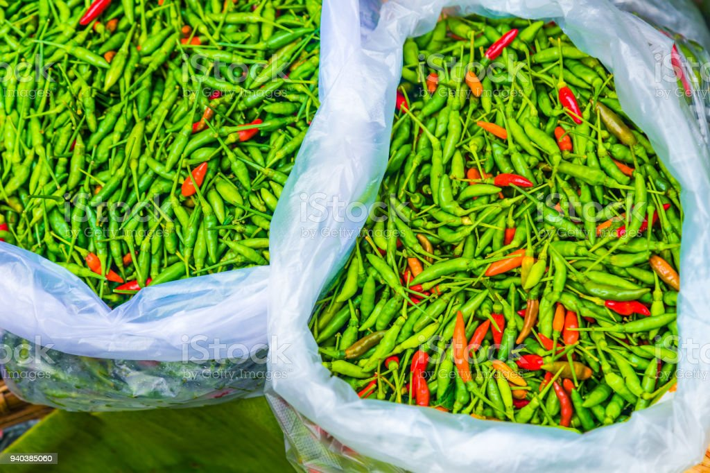 Bags full of fresh green and red spicy Thai chilis being sold at a local fresh market in Thailand stock photo