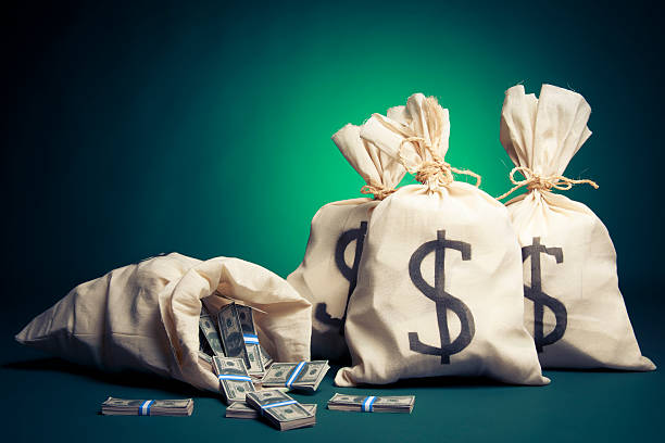 Bags full of money on a green background lots of money inside bags millionnaire stock pictures, royalty-free photos & images