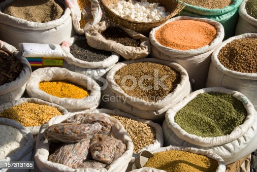 Bags full of spices, dried food herbs and cereals at an african market in Kampala, Africa. The bags stand in the sunlight that makes the colores very bright and vivid.