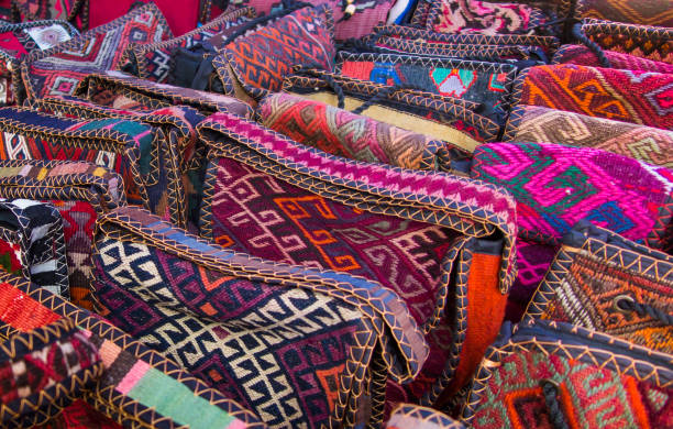 Bags, headgear, boxes made of traditional fabrics of Armenian patterns and colors lying on the stalls at the Yerevan market in Armenia Bags, headgear, boxes made of traditional fabrics of Armenian patterns and colors lying on the stalls at the Yerevan market in Armenia yerevan stock pictures, royalty-free photos & images