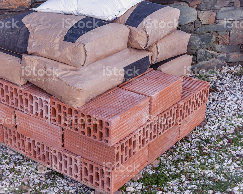 Bags of Cement and Red Bricks. Isolated stock photo
