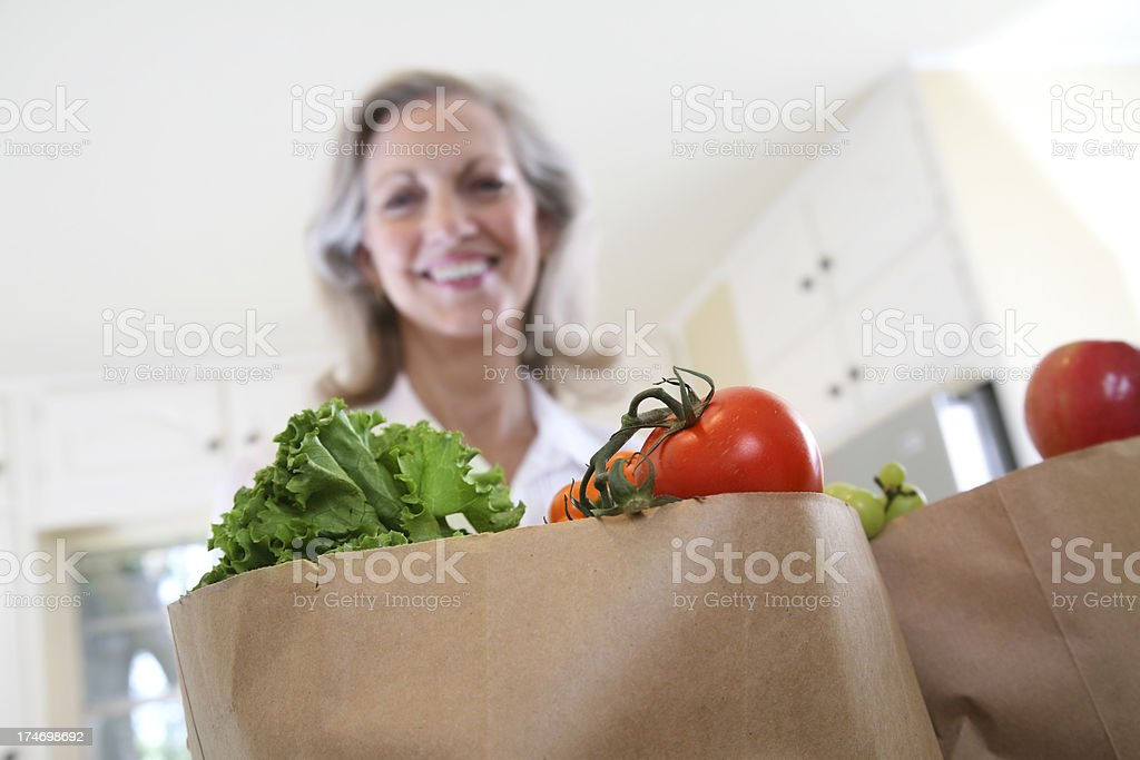 Bags of Groceries with Vegetables and a Smiling Woman royalty-free stock photo