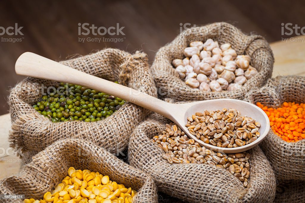 Bags of peas, chick peas, red lentils, wheat, green mung. stock photo