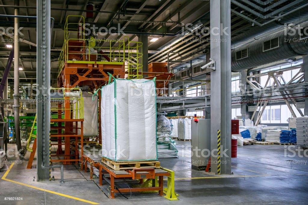 Sacos com produção química na transportadora na área de embalagem na fábrica química - foto de acervo