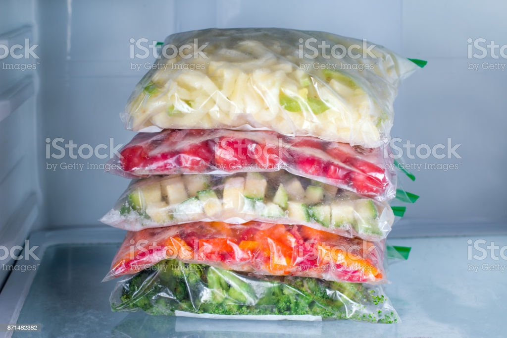 Bags with frozen vegetables in refrigerator, closeup stock photo