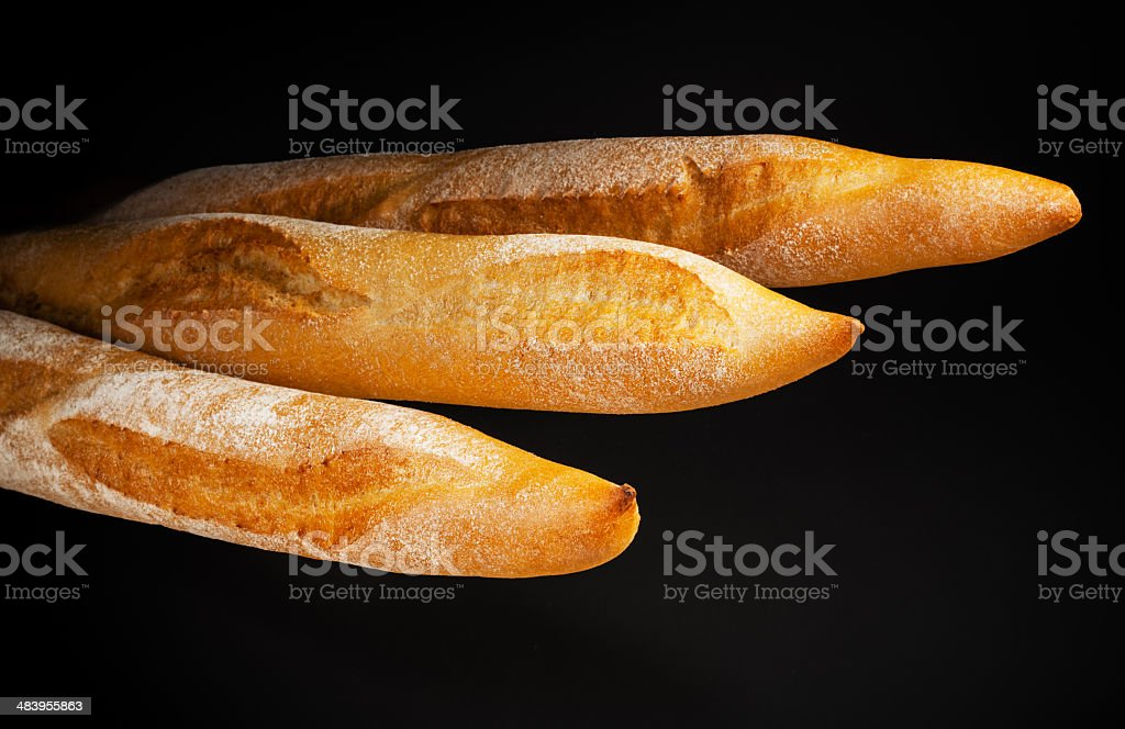 Baguette. Fresh bread isolated on black background stock photo