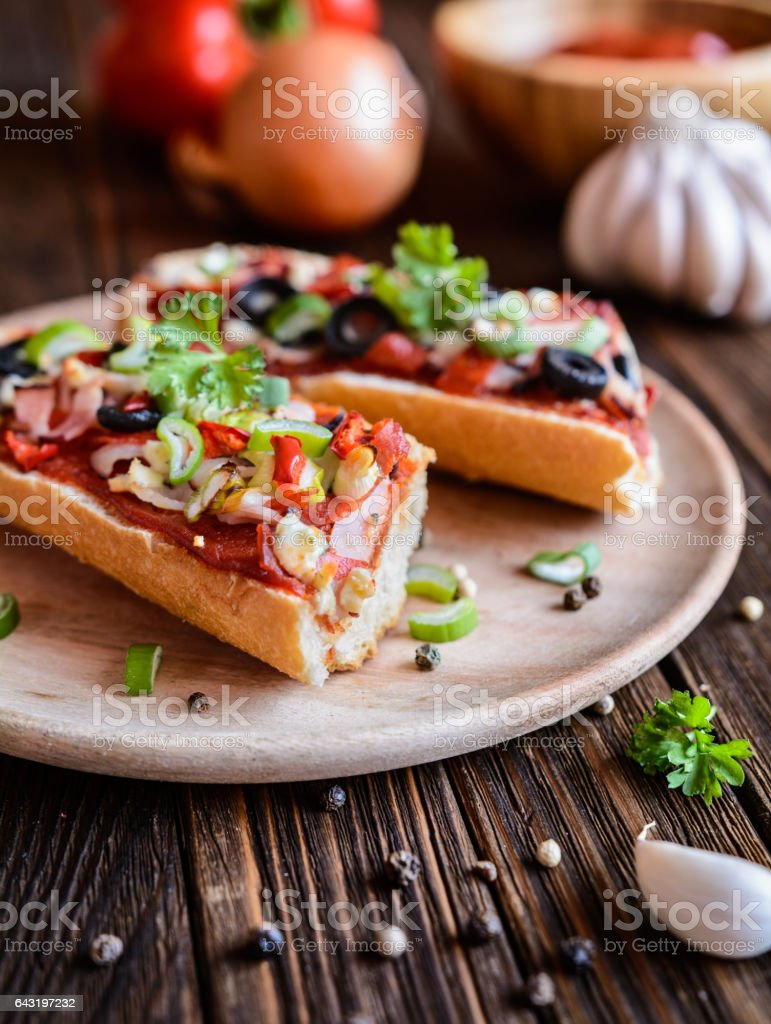Baguette pizza with bacon, salami, cheese and vegetable stock photo